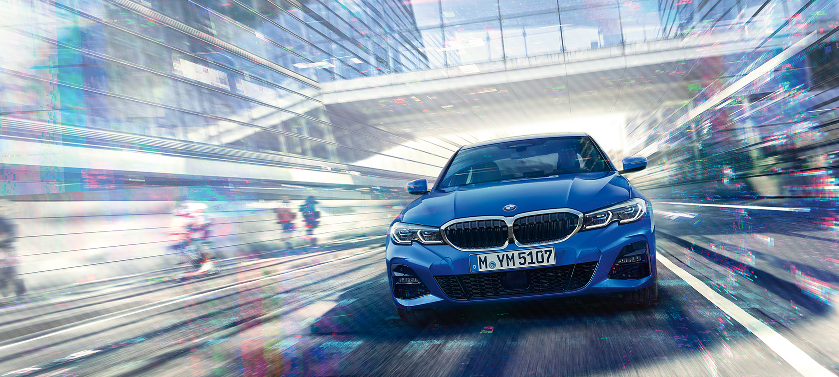 Front view of driving BMW 3 Series Sedan by day under glass building.
